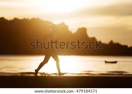Woman running on the beach at sunrise.