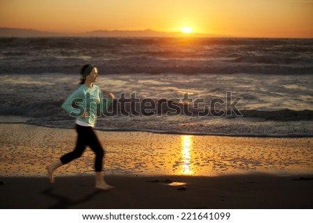 Woman running on the beach at sunset - stock photo