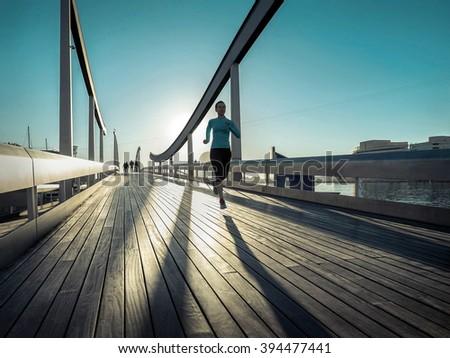 Woman running on the bridge under sunlight. - stock photo