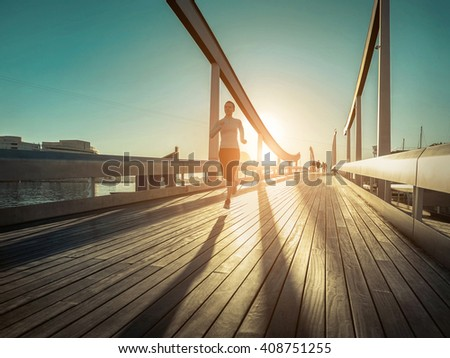 Woman running on the bridge under sunlight. - stock photo