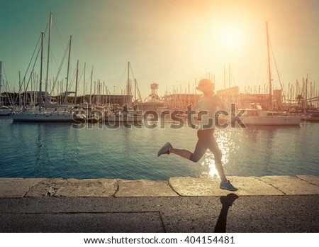 Woman running on the coastline under sunlight. - stock photo