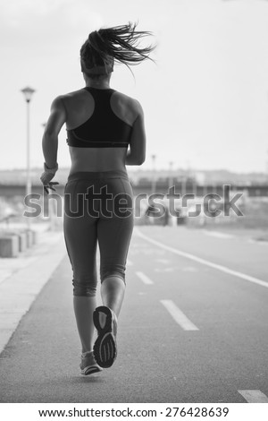 Woman running on the running track during a workout.Photo is carefully post processed to mach old black and white film look. - stock photo