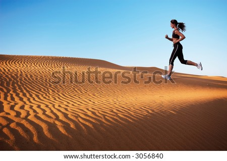 woman running on the sand dunes - stock photo