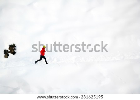 Woman running on white snow in white mountains. Adventure cross country runner on snow trail in beautiful mountain landscape. - stock photo