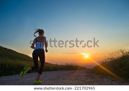 woman running outdoor on a mountain road at summer sunset - stock photo