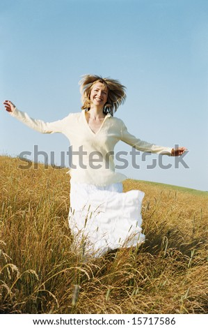 Woman running outdoors smiling - stock photo