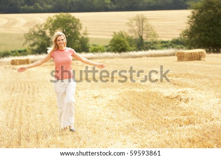 Woman Running Through Summer Harvested Field - stock photo