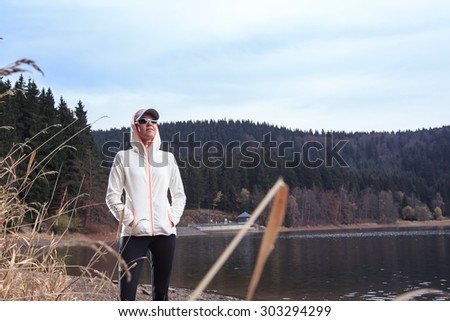 woman running through the forest by the lake