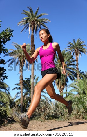 Woman running trail run at speed in tropical climate with palm trees. Beautiful multiracial Asian / Caucasian female fitness model training outdoors in summer for marathon race. - stock photo