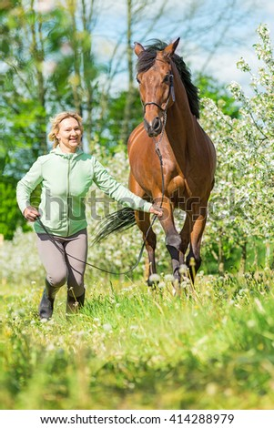Woman running with a bay horse in blooming garden. - stock photo