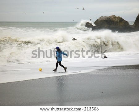 Woman runs into pounding surf to rescue a balloon at Rockaway Beach in Pacifica, CA