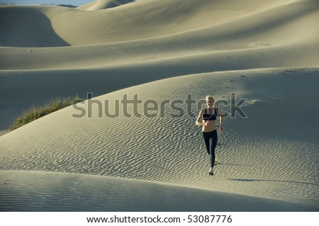 Woman runs on sand dunes. - stock photo