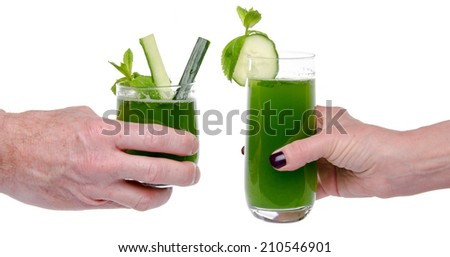 Woman's and man's hand making toast with glasses of cucumber juice, isolated on white - stock photo