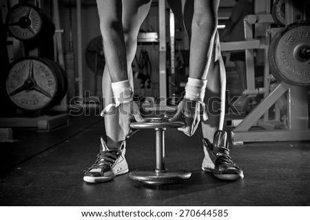Woman's arm and legs with barbells in the gym - in black and white - stock photo