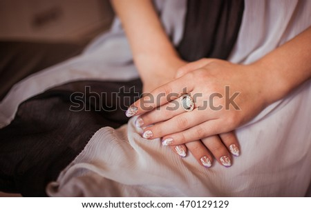 Woman's arm with a rich ring on the finger lie on her knees