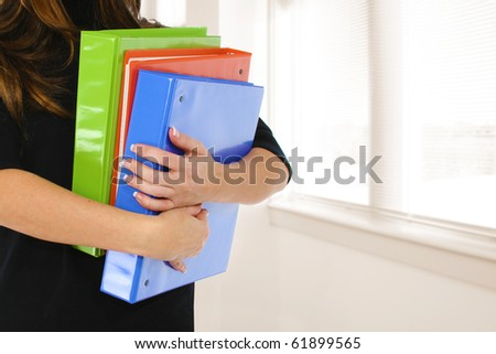 Woman's arms holding colorful binders over window copy space.