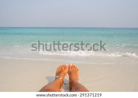 Woman's Bare Feet on the beach. Sand texture. - stock photo
