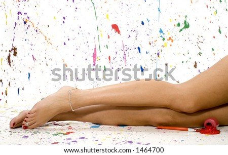 Woman's bare legs. Surounded by splattered paint. - stock photo