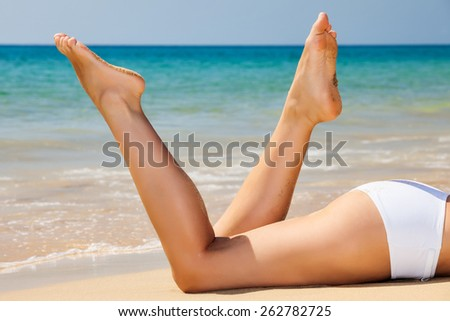 Woman's beautiful legs on the beach - stock photo