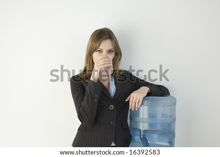 Woman, 20s, caucasian, standing at water cooler, drinking water from cup