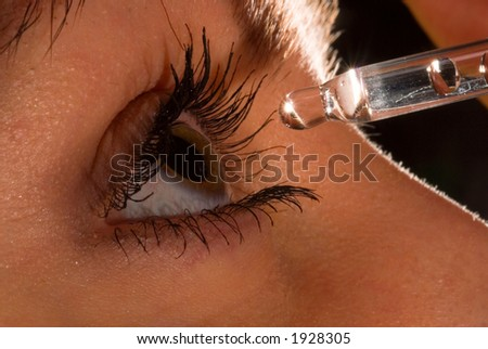 woman`s eye and eyedropper with waterdrop on tip - stock photo
