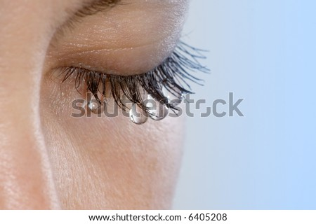 Woman's eye with several teardrops hanging on her eyelashes - stock photo
