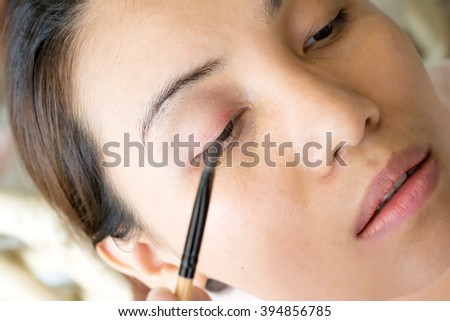 Woman's eyes getting made up with eye shadow