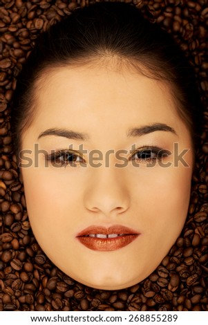 Woman's face in coffee grains. - stock photo