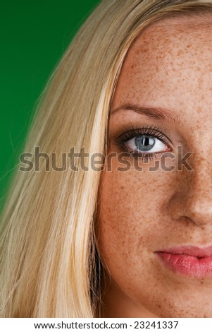 Woman's face with freckles on a green background - stock photo