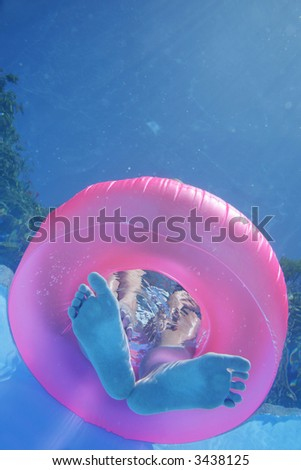 Woman's feet and rubber ring viewed from underwater - stock photo