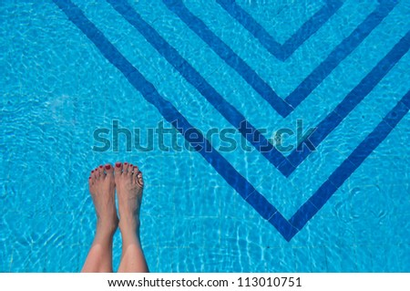 Woman's feet in a swimming pool - stock photo