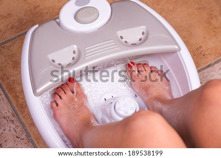 Woman's feet in a vibrating feet massager - stock photo