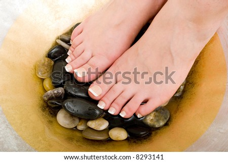 Woman's feet in bowl of water and rocks
