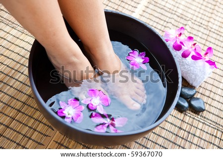 Woman's feet in foot spa bowl with orchids - stock photo