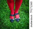 Woman's feet in shoes, against green grass - stock photo