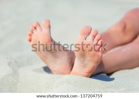 Woman's feet on the white sand near the sea.
