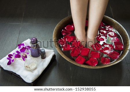 Woman's Feet Soaking in Water with Rose Petals - stock photo