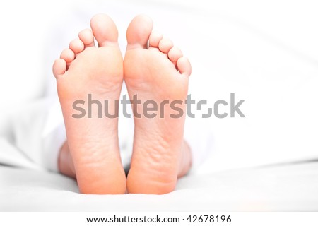 Woman's feet under the blanket. Soft Focus. - stock photo