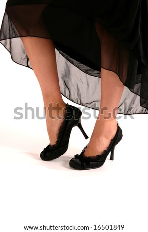 woman's feet wearing black high heel slippers with dark full dress on a white background