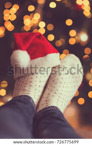 Woman's feet wearing warm winter socks and small Santa's hat, placed on the table with Christmas tree and Christmas lights in background. Selective focus
