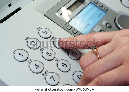 Woman's finger pushing the button on the fax machine (closeup)