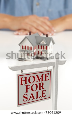 Woman's Folded Hands Behind Model House and Home For Sale Real Estate Sign In Front on White Surface. - stock photo
