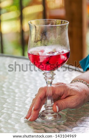 Woman's had holding stem glass of red wine. - stock photo