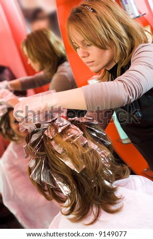 Woman's hair being painted at the hair stylist - stock photo
