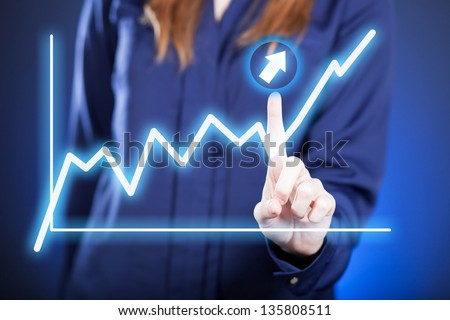 Woman's hand and growing graph on touch screen - stock photo