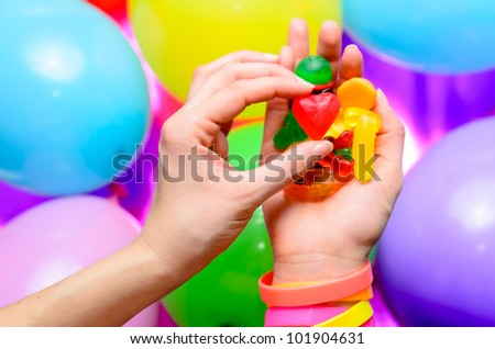 Woman's hand choosing a red jelly heart from a handful of colorful candies. - stock photo
