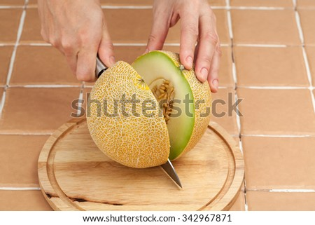 Woman's hand cuts ripe yellow melon with a kitchen knife on a wooden board - stock photo