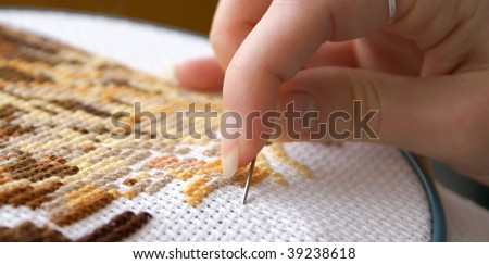 Woman's hand embroidering a picture (cross-stitch) - stock photo
