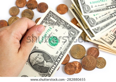 Woman's hand hold a one dollar bill on white background. Coins and bills are background. - stock photo