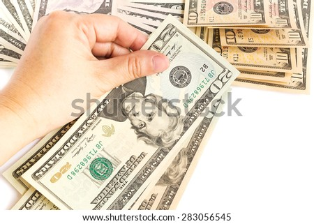 Woman's hand hold a twenty dollar bill on white background. Bills are background. - stock photo